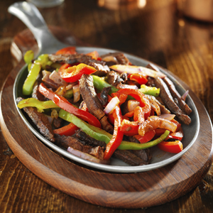 Fajitas ~ Charbroiled marinated strips of steak or chicken (or combo) with grilled onions, red and green peppers, tomatoes, lettuce, cheese, guacamole, and sour cream.