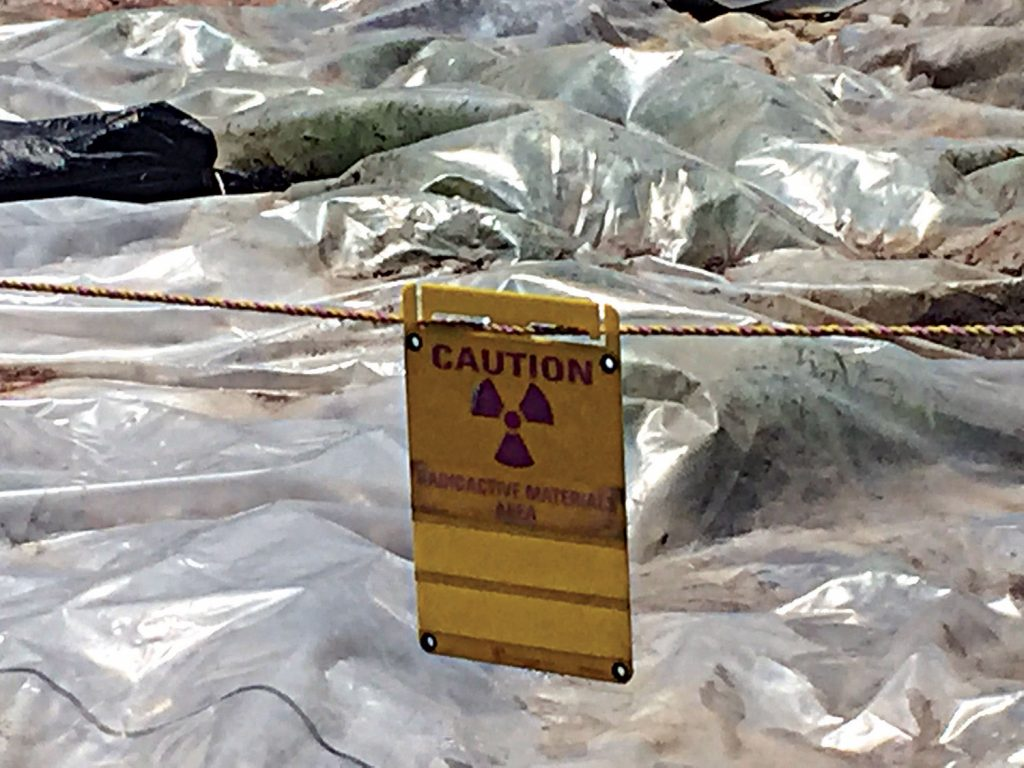 """Warning signs which read, """"Caution, radioactive materials area"""" are posted around the hazardous pile on North Ave."""